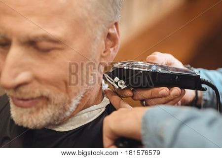 Creating neat haircut. Masterful crafty professional hairdresser standing in the salon and cutting hair of the elderly client while designing haircut