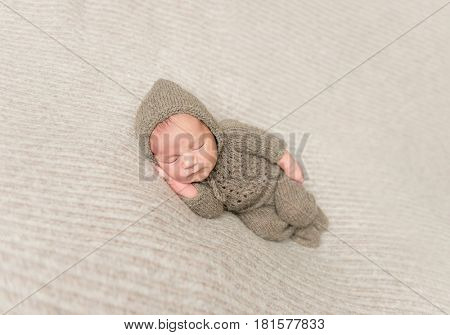 Sweet infant taking a nap in brown knitted clothes, on side, hand under his cheek