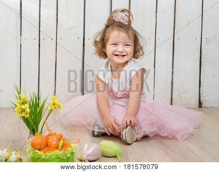 cute little girl sitting on the floor with flower pot in hands and easter decorations
