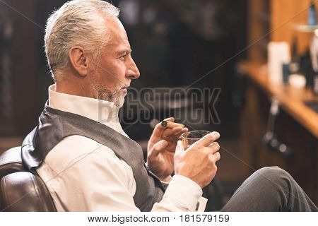 Enjoying my visit to the barbershop. Stylish confident handsome man sitting in the barbershop and holding cigar and beverage while enjoying free time