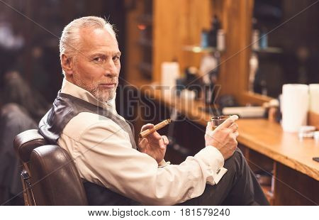 Enjoying atmosphere in my barbershop. Bearded confident senior man sitting in the barbershop and holding cigar and beverage while enjoying free time