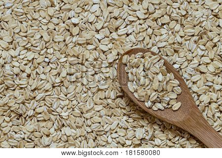 Pile of smashed oat seed with wooden spoon, close up