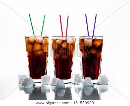 three glasses of cola with ice and straws on a white background. soft drinks and
