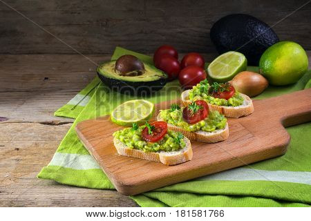 avocado cream or guacamole on baguette sandwiches with ingredients like lemon onion and tomatoes on a rustic wooden board healthy vegetarian party snack copy space selected focus