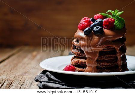 chocolate pancake with blueberries raspberies and chocolate sauce