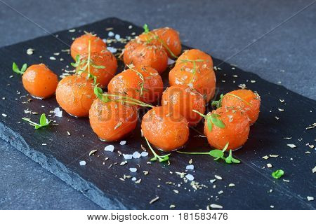 Honey glazed baby carrots with sea salt and thyme on a grey abstract background. Healthy eating concept. Fastening food. Healthy meal