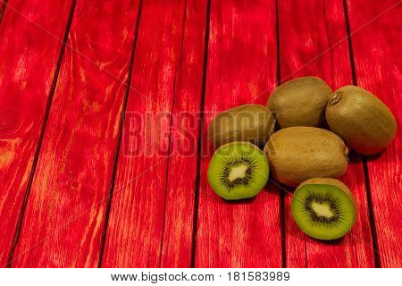 A photo shows kiwi fruit placed on a red made from a wooden background. Some of the fruits are crossed showing juicy flesh and black pips.