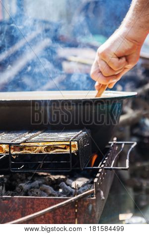 On the grill is a cauldron in which to cook meat and vegetables. The man's hand prepares food.