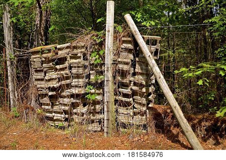 Old cement  building blocks are stacked and stored along a fence line in a woods