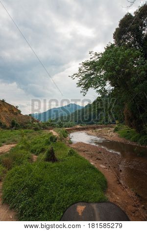 Landscape with riverbed with low water in the rain forest of Khao Sok sanctuary, Thailand