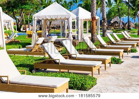 Tropical Beach Resort With Umbrellas And Lounge Chairs