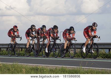 ENKHUIZEN, THE NETHERLANDS - JULY 2 ,2016: Cyclists ride in a row, during a time trial contest for cyclists on the car dike Lelystad and Enkhuizen