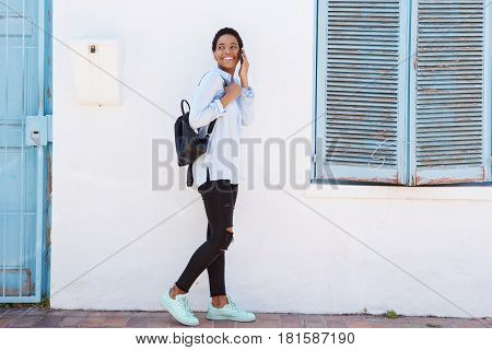 Full Length Young African Woman Walking With Cellphone And Bag