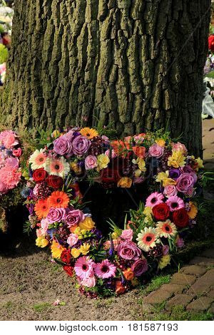 Heartshaped sympathy flowers or funeral flowers near a tree