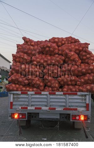 21,Dec ,2014 ,Beijing, China. Onions in red plastic mesh sacks and bags in grid on a car