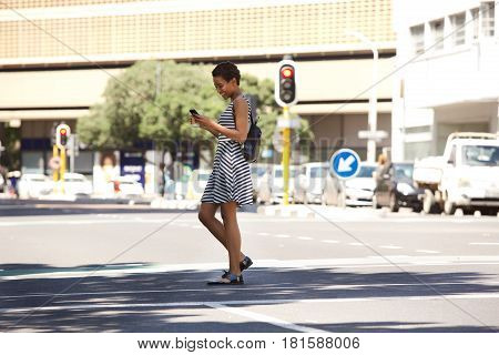 Young Woman Walking On Street With Mobile Phone