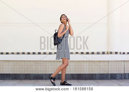 Young Black Woman Walking On Street With Mobile Phone