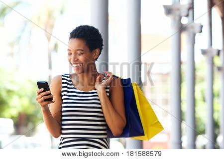 African American Woman Walking With Cellphone And Shopping Bags