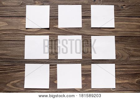 five white square notes on wooden background, square formation