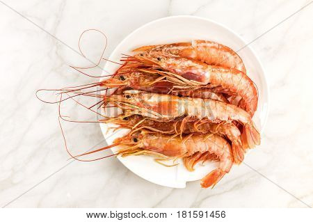 Raw shrimps on a plate, shot from above on a white marble table with a place for text