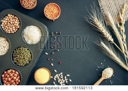 Assortment of legumes grains and seeds. Various types of grains rice bean spices and herbs in bowls on a black background top view.