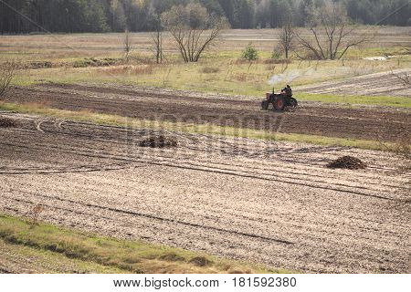 The tractor plows the field in the spring.