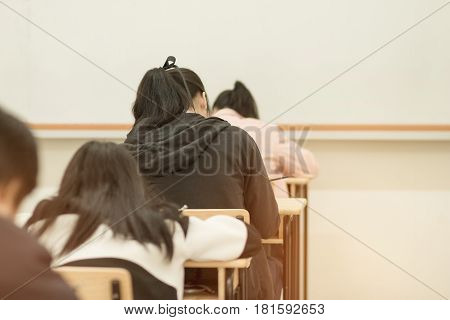 blurred of girl school students in uniform attending examination in a classroom in educational school: view of college people having exams in class on seat rows