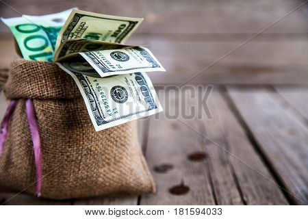 money in burlap sack on wooden background and