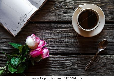 Fresh roses with diary and cup of coffee on wooden table, top view. flowers, hot drink and