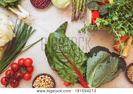 Fresh spring vegetable,herbs and legumes over concrete background. Top view, vintage toned image, blank space