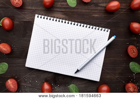 Notepad with a handle surrounded by sheets of arugula and small tomatoes with salt on a wooden background. Top view.