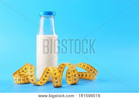 Bottle of milk with centimeter on blue background
