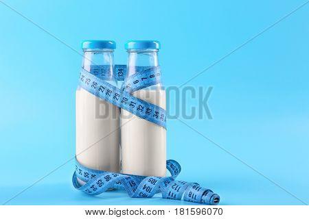 Bottles of milk with centimeter on blue background