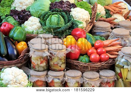 Fresh colorful vegetables and pickles in jars .