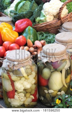 Pickles in jars and fresh colorful vegetables close up image