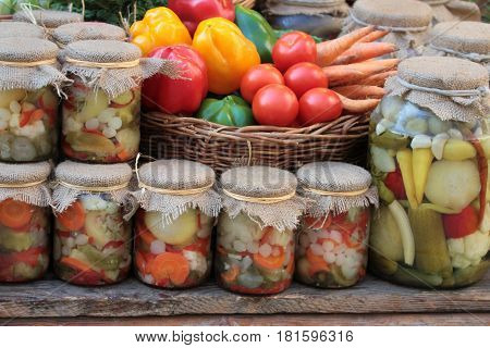 Pickles in jars and fresh colorful vegetables