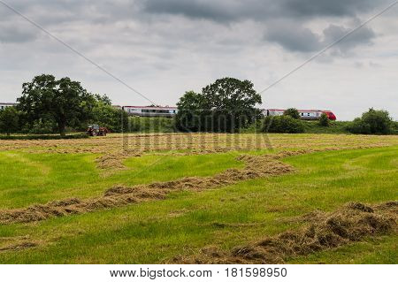 A Virgin Train Passes A Tractor On A Field