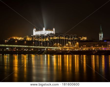 Lights from Bratislava reflect on the waters of the Danube River at night.