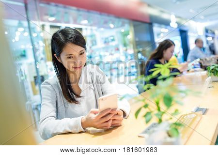 Woman sending sms on mobile phone in restaurant