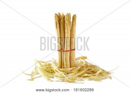 bunch of white asparagus fresh and organic standing in asparagus peel isolated on a white background