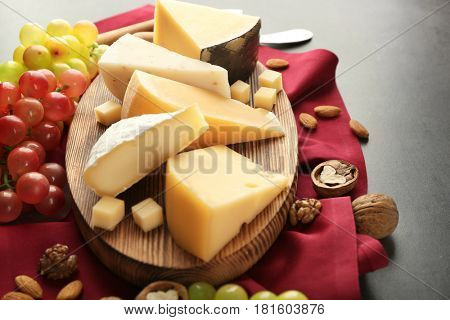Cheeseboard with grape and nuts on red napkin