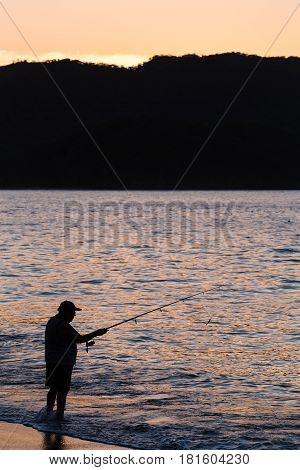 A tico fishes on a beach at Guancaste in Costa Rica at dusk.
