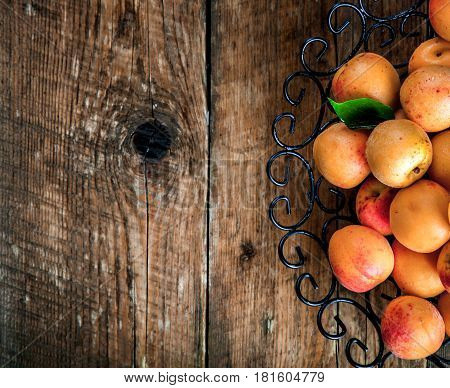 Bowl of harvested apricots. Fresh apricots on wooden background and
