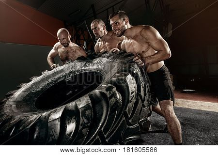 cross strongman training - three men flipping big tire