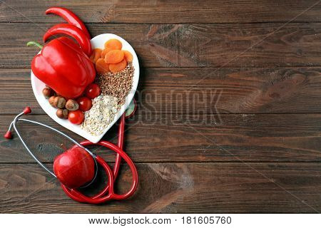 Healthy food in heart shaped plate on wooden background