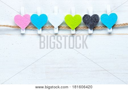 Colorful hearts on a twine on old white natural wooden background. Flat lay top view. Copy space on the bottom.