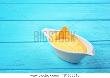 Gravy boat with tasty cheese sauce on color wooden background