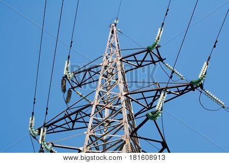Power transmission tower. High voltage. Wires. Insulators. Blue background.