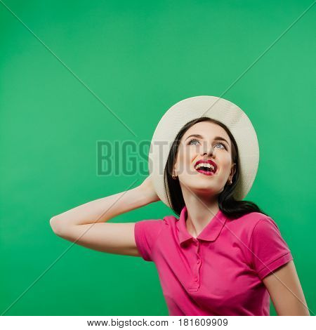 Joyous Toothy Smiling Girl with Long Hair is Posing in Cowboy Hat and Bright Pink Shirt on Green Background. Closeup Portrait of Pretty Brunette with Professional Makeup in Studio.