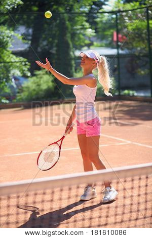 Pretty girl in cap serves tennis ball on court at sunny summer day, back view
